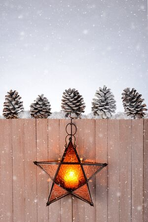 five star: A star shaped lantern hanging on a rustic wood fence. Five pine cones are lined up on top of the fence on a winter evening with snow flakes.