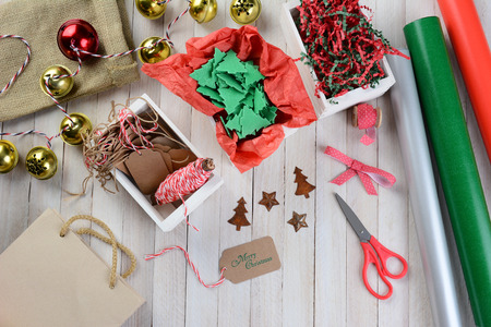 Overhead view of Christmas wrapping supplies on a rustic wood table. Scissors, ribbon, bells, tags, paper rolls, gift bag, string, ornaments and crepe paper are displayed. Stock Photo