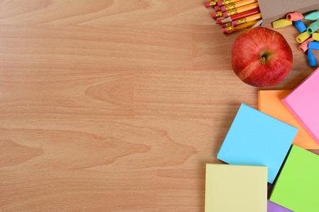 convivencia escolar: Alto ángulo de volver a la escuela la naturaleza muerta sobre una mesa de los profesores de madera. Una manzana, blocs de notas, lápices y gomas de borrar con copia espacio.