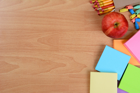 pencil box: High angle back to school still life on top of a wood teachers desk. An apple, note pads, pencils and erasers with copy space.