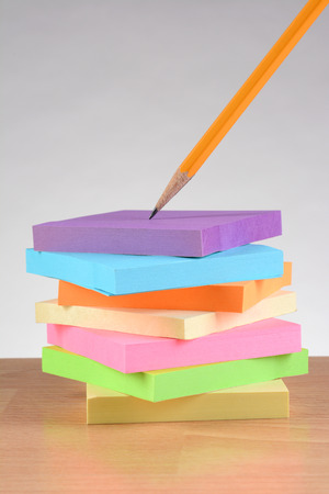 schoolroom: Colorful note pads and pencil on teachers desk. Vertical format against a light to dark gray background. Stock Photo