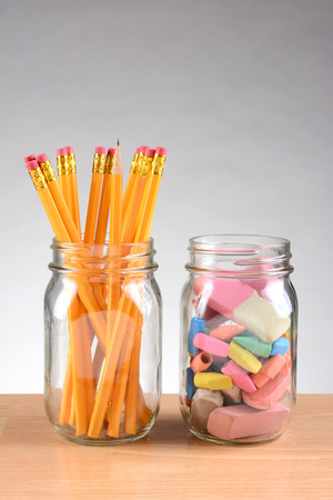 schoolroom: Closeup of two jars on a teachers desk with pencils and erasers. Vertical format on a light to dark gray background with copy space. Stock Photo