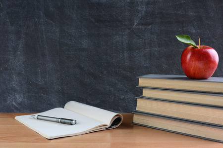 closeup: Closeup of a teachers desk with books, paper and pen and a red apple in front of a chalkboard. Horizontal format with copy space.