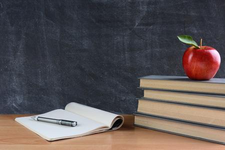 manzana: Primer plano de una mesa de los profesores con los libros, papel y lápiz y una manzana roja delante de una pizarra. Formato horizontal con espacio de copia.