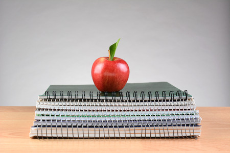 centered: Closeup of a stack of spiral notebooks on a teachers desk with a single red apple centered on top. Back to school concept with copy space on a light to dark gray background.