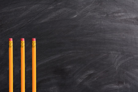 schoolroom: Three new pencils standing in front of a chalkboard with eraser marks. Horizontal format with copy space. Back to School concept.