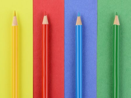 schoolroom: Overhead view of four colored pencils on matching colored paper. Closeup in horizontal format. Back to School concept.