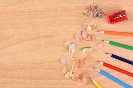 schoolroom: High angle view of six colored pencils on a school desk with a sharpener and shavings. Horizontal with copy space. Back to school concept.