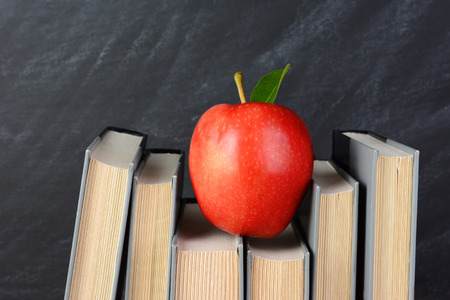 atop: A red apple perched atop text books on a teachers desk with an out of focus chalkboard behind.