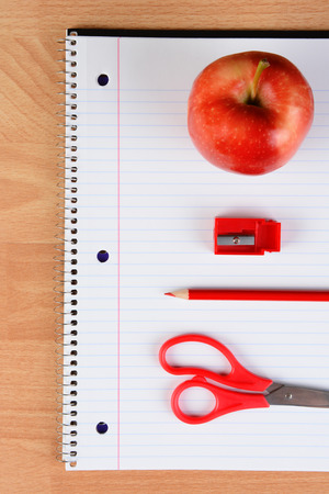 spiral notebook: Overhead view of a red pair of scissors, red pencil, sharpener and apple on an open spiral notebook on a wood desk. Back to school concept.