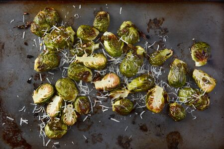 sheet metal: Roasted Brussels Sprouts with grated parmesan cheese. Horizontal format form a high angle. Stock Photo