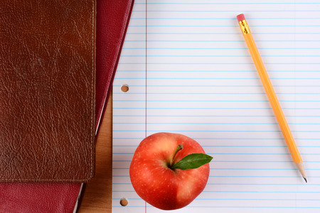 schoolroom: Overhead view of an apple  and pencil on notebook paper with school books. Closeup in horizontal format. Back to School concept.