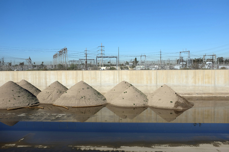orange county: Piles of sand in the Santa Ana River in Orange County, California. Crews clean up the sand that collects in the concrete lined river, for distribution to local beaches.
