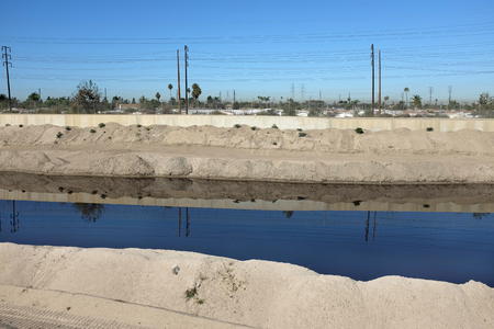 mounds: Mounds of sand line the Santa Ana River in Orange County, California. Crews clean up the sand that collects in the concrete lined river for distribution to local beaches.