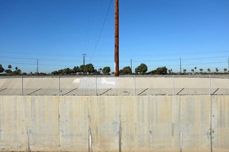 retaining: A power pole and concrete retaining wall along the Santa Ana River in Orange County, California