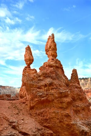 badland: Hoodoos in Bryce Canyon. A hoodoo, also called a tent rock, fairy chimney, and earth pyramid, is a tall, thin spire of rock that protrudes from the bottom of an arid drainage basin or badland.