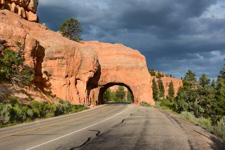 natural wonders: Red Canyon tunnel with Storm Clouds. The tunnels were opened in 1925 to Celebrate the opening of Bryce Canyon National Park - The are the Gateway to Natural Wonders.