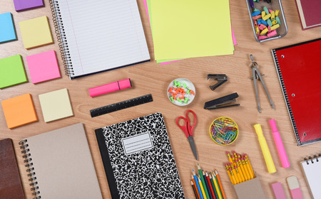 high angle shot: High angle shot of school supplies laid out on a wood desk. Back to School concept with paper, pads, pencils, notebooks, scissors, erasers and more. Horizontal format at an angle.
