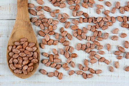 pinto: Overhead view of a wood spoonful of pinto beans surrounded by more loose beans. Horizontal format on a rustic whitewashed wood table.
