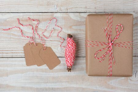 three presents: Overhead view of blank gift tags a spool of string and a plain brown paper wrapped present on a rustic whitewashed wood table.