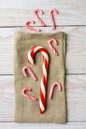 sized: Overhead view of different sized Candy canes on a burlap bag and three on wood surface. On a rustic wood table in vertical format