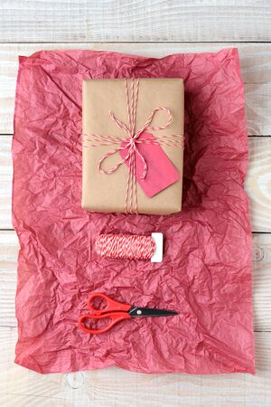 tissue paper: Overhead view of a Christmas present wrapped in plain brown paper, a spool of string and scissors on a sheet of crumpled red tissue paper. The objects are on a rustic whitewashed wood table.