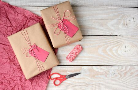Overhead view of two Christmas presents wrapped in plain brown paper and tied with red and white string, Scissors,, spool of string and red tissue paper with copy space.
