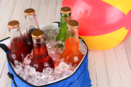 ice chest: Closeup of a cooler with soda bottles and ice on a rustic wood table with a beachball in the background.