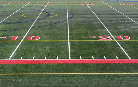 sideline: Closeup of the yardage markers on a football field. The numbers are in red on an artificial turf field.