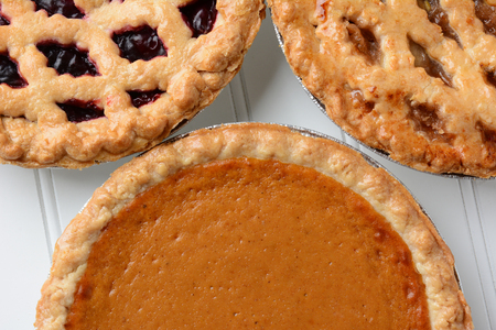 Closeup of three different fresh baked holiday pies.  Pumpkin, apple and a berry pie are shown.