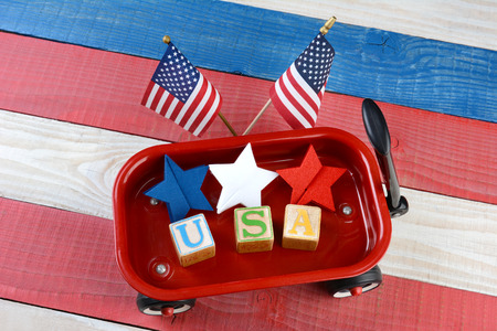 summertime: A childs toy wagon with red white and blue stars and blocks spelling USA. Two American Flags are behind the wagon on a patriotic red white and blue wood picnic table. Great for American holiday projects. Stock Photo