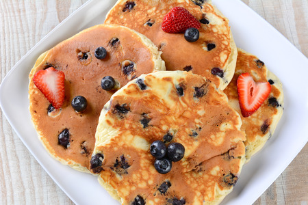 griddle: Overhead closeup view of a plate full of fresh homemade pancakes with blueberries and strawberries.