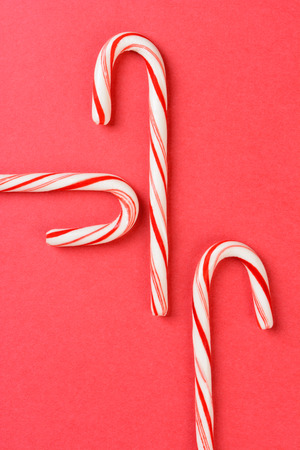high angle shot: High angle shot of three Christmas candy canes on a red background. The peppermint sticks run in different directions and out of the frame. Vertical format with copy space.