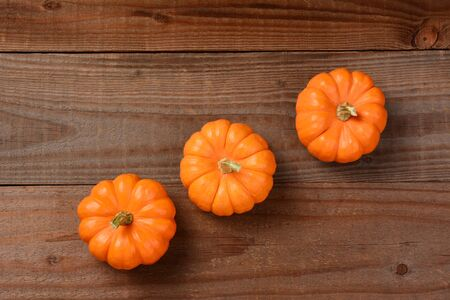 Three mini pumpkins on a dark wood background. Arranged at an angle leaving copy space at the top and bottom.