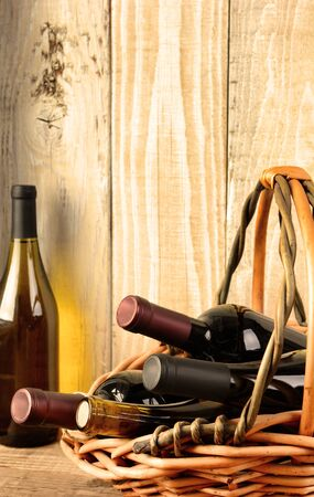 Closeup of a wine still life with warm afternoon window light. A basket with assorted bottles and a chardonnay bottle in the corner against a rustic wood background. Bottles have no labels.