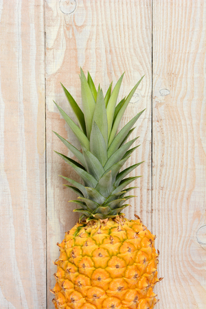Closeup of a fresh ripe pineapple against a rustic white wood background. Vertical format with copy space. Zdjęcie Seryjne