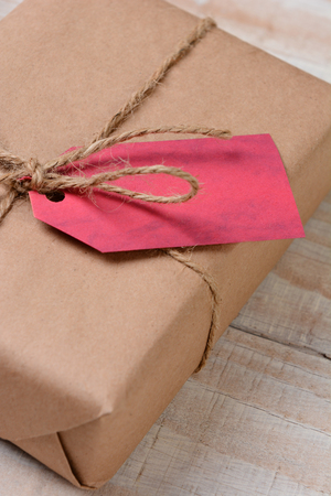 wrapped present: Closeup of an eco friendly christmas present - wrapped in recyclable plain brown paper and tied with twine. Vertical format on a rustic wood table. Shallow depth of field with copy space.