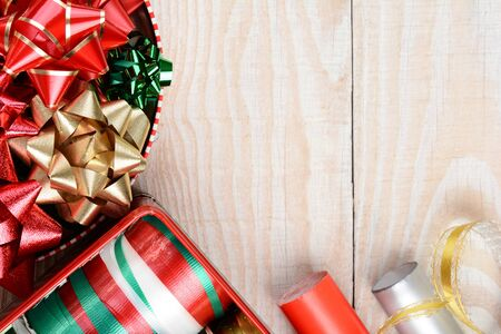 tins: Tins of holiday ribbon and bows and wrapping paper on a rustic wood background with copy space. Stock Photo