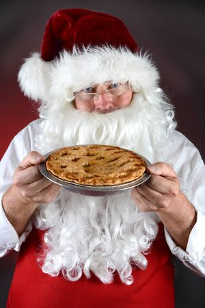st  nick: Santa Claus holding a fresh baked apple pie. Santa is wearing a red apron against a light to dark red background. Vertical format.