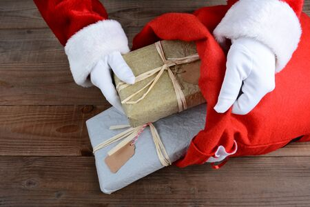 bag: Closeup of Santa Claus putting packages in his bag on Christmas Eve. Stock Photo