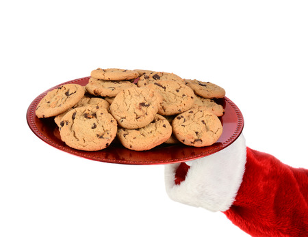 st nick: Closeup of Santa Claus hand holding a tray of cookies over a white background. Stock Photo
