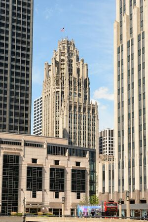 tribune: CHICAGO, ILLINOIS - AUGUST 22, 2015: Tribune Tower. The Gothic style building is seen between some of the more modern architecture in Downtown Chicago.