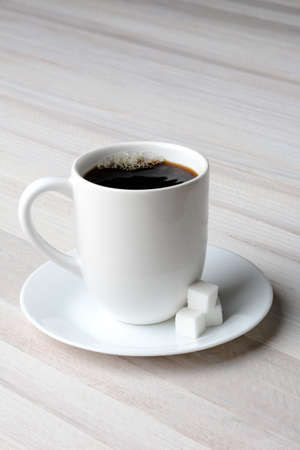 poured: A mug of fresh poured coffee with sugar cubes on the saucer. Vertical format on a rustic white wood table with copy space.