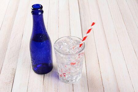 Une bouteille d'eau bleue avec un verre plein de glace et une paille rayée rouge et blanche. Format horizontal sur une table en bois rustique.