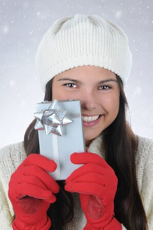 knit cap: Closeup portrait of an attractive teenage girl wearing a knit cap holding a small Christmas present in front of her. Vertical format with a snowy background.