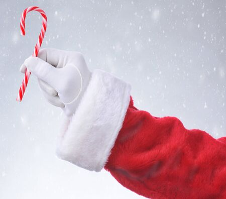 Closeup of Santa Claus holding a candy cane in his fingers over a snowy background.