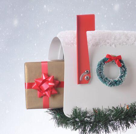 buzon: Un regalo de Navidad envuelto sobresale de un buzón abierto decorado para las vacaciones. Plaza de la composición con el fondo cubierto de nieve. Foto de archivo