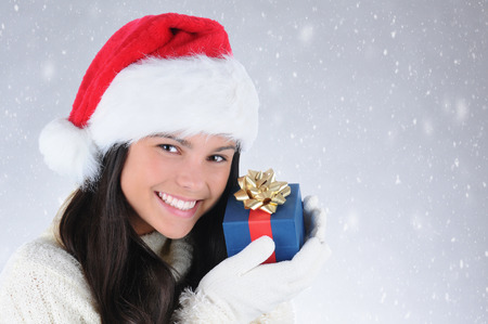 Smiling teen girl wearing a Santa Claus hat holding a small Christmas present up to her face. Horizontal format with snowy background. photo