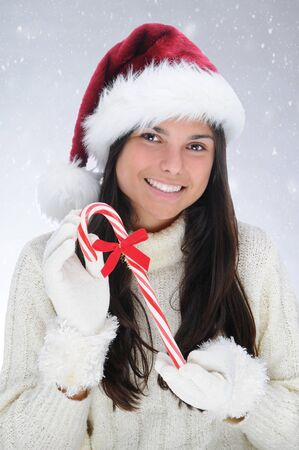 Teen girl in a Santa Claus hat holding Christmas candy cane. Horizontal format with snowy background. photo
