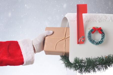 Santa Claus putting a plain brown paper wrapped package ina  mailbox, Horizontal format with a snowy background. Stock Photo
